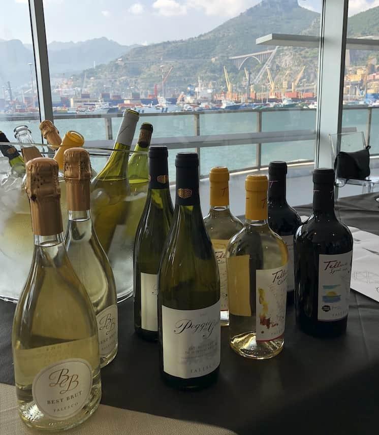 Bottiglie di vino ad In Vino civitas sullo sfondo del porto di Salerno